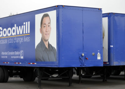 Partial wrap. The vehicle is painted blue. The text, graphics, and photo are large format vinyl graphics.
