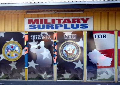 A wall of window graphics at a military surplus store brighten an older building.